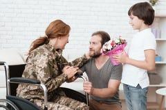 从军队返回的轮椅的妇女退伍军人 儿子和丈夫是愉快看她 免版税库存照片