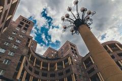 从冠上的底部的看法巨大的圆的大厦、路灯到底和多云天空,耶烈万 免版税图库摄影