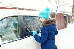 从冬天雪的年轻十几岁的女孩清洗的白色汽车 库存图片