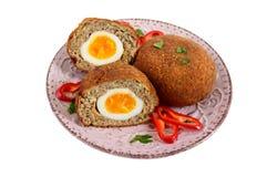 从切好的肉被充塞的煮沸的鸡蛋的水多的炸肉排在被隔绝的一块陶瓷板材 免版税库存图片