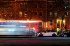 从加速在一条空的哈林街道下的纽约救火车或救护车的Lightstreaks,后在晚上 免版税库存图片
