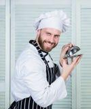 从厨师的特价优待 天的盘 厨师准备好烹调 围裙和帽子举行盘子的确信的人 专业人员 免版税库存照片