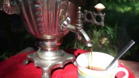 从古色古香的俄国水壶`俄国式茶炊`的倾吐的茶户外 股票视频