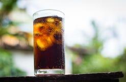 从可乐的饮料在与冰的玻璃在棕色木头,饮料在夏天是苏打水 库存照片