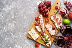 从各种各样的快餐设置、Bruschetta或者地道传统西班牙塔帕纤维布、红葡萄酒和葡萄在灰色背景 竞争 免版税库存照片