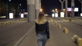 从后侧方的英尺长度美好少妇走freeby一条空的路在都市城市 白肤金发女孩微笑,摆在 股票视频