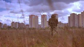 从后面、被隔绝的男性在军队制服和伪装神色的射击,wolking直接地对有自动炮的城市 股票录像