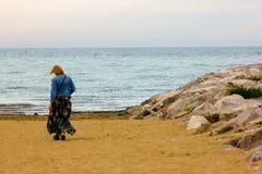 从后面一会儿走在海滩的妇女 库存照片