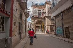 从后面的妇女在有步行沿着向下街道的孩子的一件红色夹克 哈瓦那 古巴 免版税库存照片