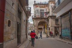 从后面的妇女在有步行沿着向下街道的孩子的一件红色夹克 哈瓦那 古巴 库存图片