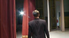 从后面的看法,艺术家在幕后出场与话筒的并且开始唱歌 股票视频
