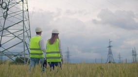 从后面的看法:小组一个高压能源厂的工程师有片剂的和图画走并且谈论a 影视素材