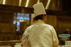 从后面看见的繁忙的女性厨师在一家日本餐馆,东京,日本 免版税图库摄影