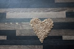 从向日葵种子做的心脏在灰色厨台上面 库存图片
