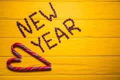从咖啡的新年文本在黄色木板条背景 背景新年度 免版税库存图片