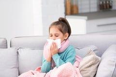 从咳嗽的女孩在沙发的痛苦和寒冷 免版税库存图片