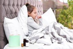 从咳嗽的女孩痛苦和寒冷在床上 免版税库存图片