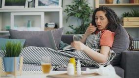 从咳嗽的少女使用膝上型计算机的痛苦和鼻涕在家 股票录像