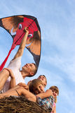 从四个人的系列蓝天飞行风筝。 库存图片