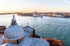从圣在盛大海峡的乔治Maggiore的鸟瞰图有往圣玛丽亚della致敬教会的小船的  图库摄影