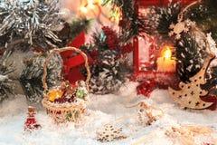 从圣诞老人的小多彩多姿的玻璃瓶在与礼物的一个柳条筐在红色灯笼和新年` s装饰的背景 免版税库存图片