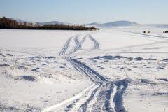 从在一个多雪的湖的雪上电车追踪有渔夫的在背景中 库存照片