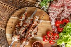 从在有新鲜蔬菜的一个木板计划的猪肉的开胃烤肉串 在木背景的静物画 库存照片