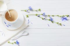 从在杯子的苦苣生茯喝在白色木桌上 免版税库存照片