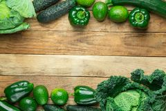 从在被风化的板条谷仓木头的新鲜的未加工的有机绿色菜皱叶甘蓝夏南瓜黄瓜甜椒鲕梨构筑 免版税库存图片