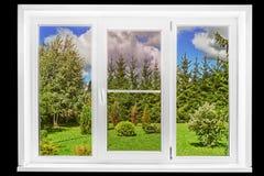 从在黑色在一个晴朗的夏日隔绝的一个乡间别墅窗口的庭院视图 免版税库存照片