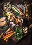 从地方市场的各种各样的五颜六色的有机菜成份在与罐,匙子,板材的黑暗的土气厨房用桌背景 库存图片