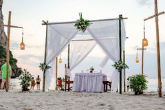 从地面的透视,被定调子的白色 游人享受在海滩的日落视图 在为a装饰的沙子集合桌上 免版税库存照片