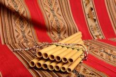 从坐反对一件红色纺织品的南美的锅管 图库摄影