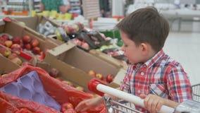 从坐在台车的箱子的滑稽的小男孩采摘苹果,在家庭购物期间在大型超级市场 股票录像