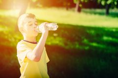 从塑料瓶的小男孩饮用水 免版税库存图片