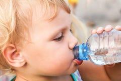 从塑料瓶的白种人儿童饮料水 库存照片