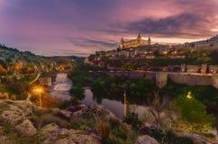 从塔霍河的另一边看见的托莱多在与Alcà ¡ zar de托莱多的日落照亮了 免版税库存图片