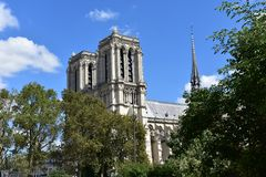 从塞纳河步行的巴黎圣母院 法国巴黎 塔和尖顶 与cluds的好日子 库存照片