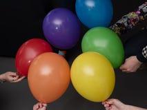 从多彩多姿的彩虹气球的圈子在手上 库存图片