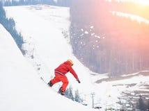 从多雪的小山的顶端年轻男性挡雪板骑马与在日落的雪板在滑雪胜地 免版税库存图片