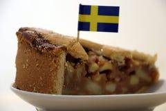 从大圆形蛋糕的苹果蛋糕三角裁减与瑞典牙签旗子 免版税库存照片