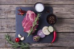 从大理石牛肉的生肉牛排与在石板材的菜 顶视图 库存图片