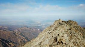 从大阿尔玛蒂峰顶的看法到市阿尔玛蒂 石岩石、蓝天、云彩和黑暗的烟雾 库存照片