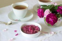 从大马士革的瓣的果酱上升了,一个杯子绿茶和一个花瓶在一张轻的桌上的玫瑰 土气样式 免版税库存照片