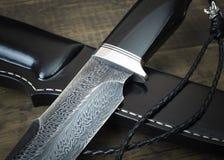 从大马士革马赛克的猎刀在木背景 手工制造皮革的鞘 免版税库存图片