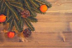 从天然材料-圣诞树分支,锥体,空泡灯笼的圣诞节背景在木的 图库摄影