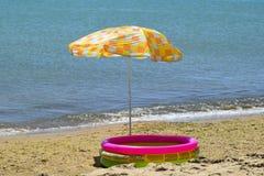 从太阳的沙滩伞在海滩 黑海 免版税库存照片