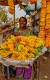 从她的摊位的微笑的妇女出售花 库存图片