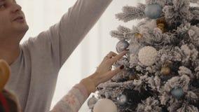 从妈妈的愉快的年轻家庭,爸爸和小女孩装饰一棵圣诞树 影视素材