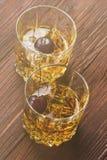 从威士忌酒的鸡尾酒用樱桃在两块玻璃中在木后面 免版税库存照片